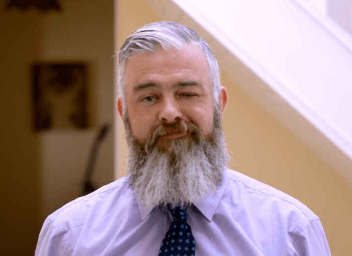 A man with grey hair and a long beard wearing a lavender coloured shirt and a navy tie in a living room.