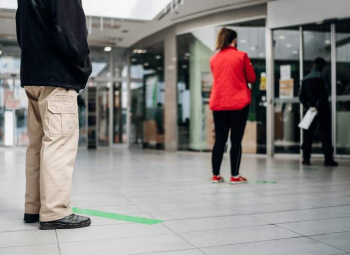 A queue of customers physical-distancing outside of a shop, with lines marked on the floor to show them how far to stand apart.