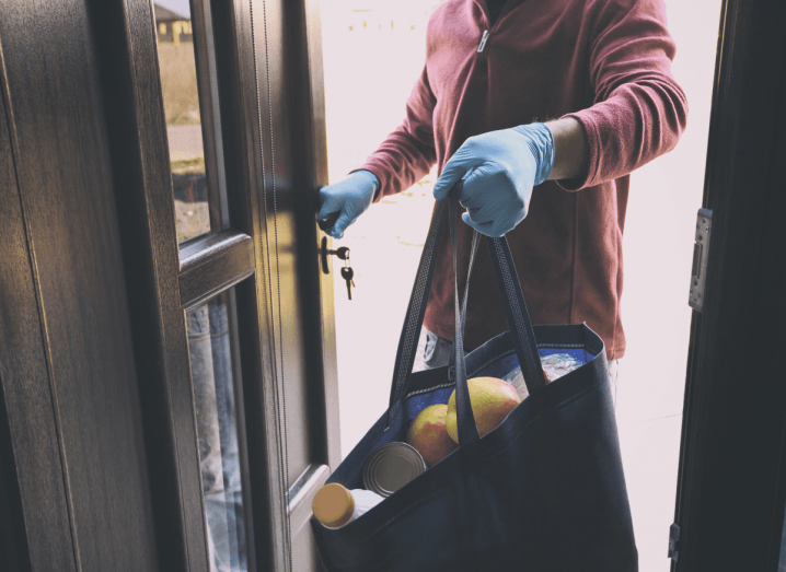 A person in a red fleece top wearing blue silicon gloves delivering a bag of groceries through a doorway.