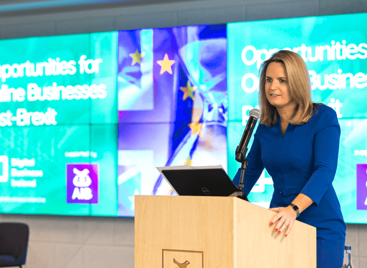A woman in a blue dress stands at a podium in front on blue screens that have the AIB logo on them.