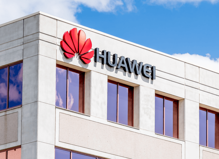 The Huawei logo on an office building under a blue sky with some clouds.
