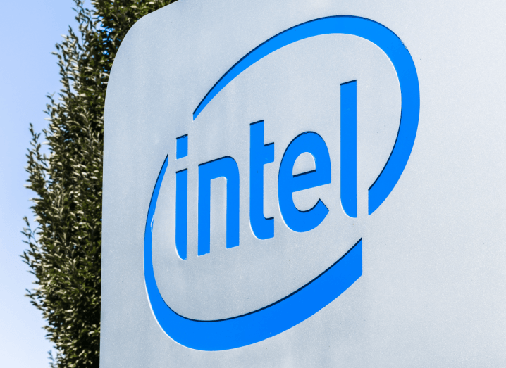 The Intel logo on a sign in front of a tree.