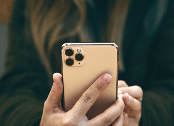 A person with long hair wearing a green jacket holds an iPhone 11.