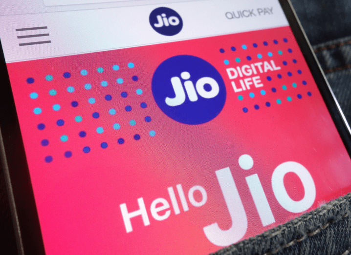 The Jio website displayed on a smartphone in a back pocket of a pair of jeans.