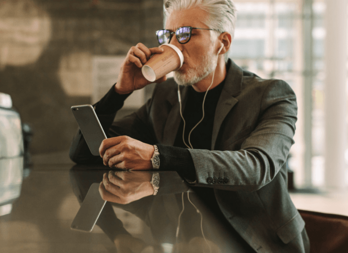 A man in a cafe holding a smartphone with earbuds plugged into his ear. He has white hair and glasses.