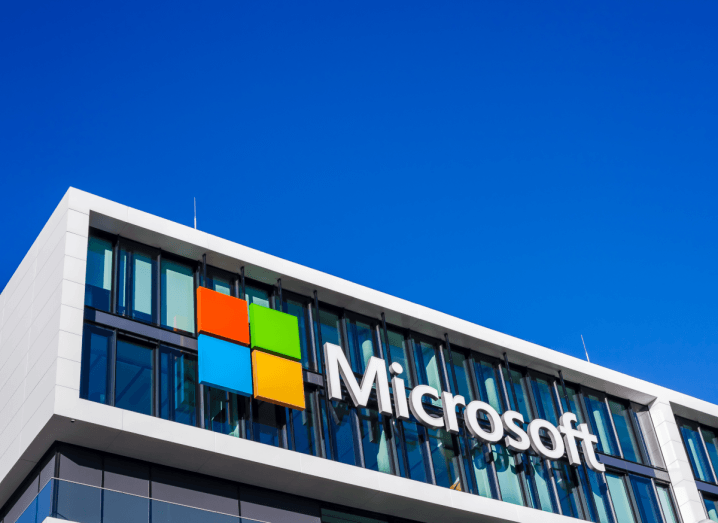 The Microsoft logo on the side of a building under a blue sky.
