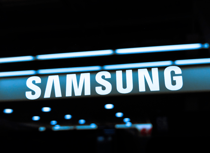 The Samsung logo on a black glass surface, with reflections of lights from a Samsung store dotted underneath the logo.