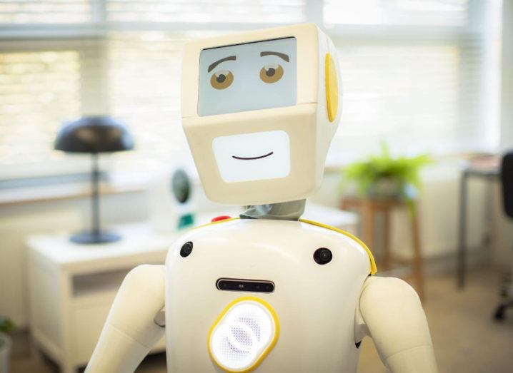 A white robot with a smile on its face.