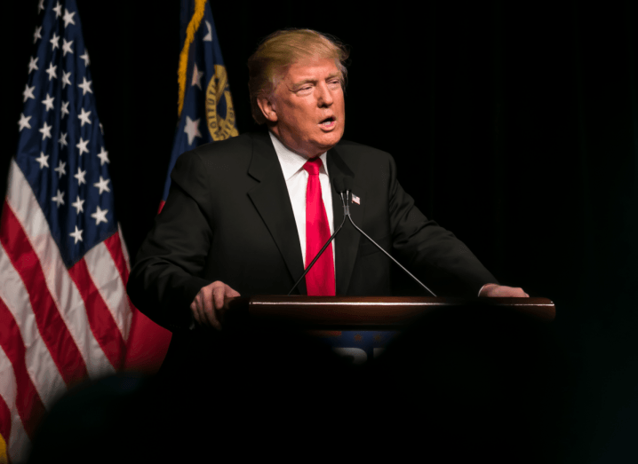 Donald Trump standing at a podium wearing a black suit and a red tie in front of an American flag.