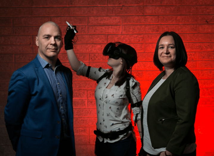 A man in a navy suit and a woman in a green jacket look towards the camera in a room with a red wall. Between them, in the background, there is a young woman using a VR headset.