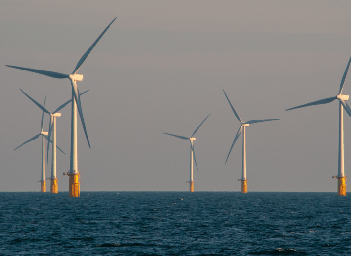 An offshore windfarm in a dark sea with seven turbines visible in the photograph.