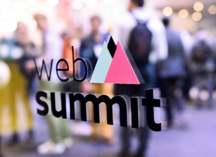 The Web Summit logo on a glass wall with people behind it.