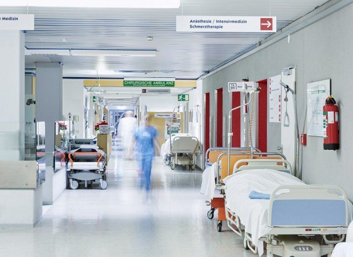 Busy hospital corridor lined with beds.