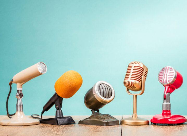 Assorted radio microphones on a wooden table against an aquamarine background.