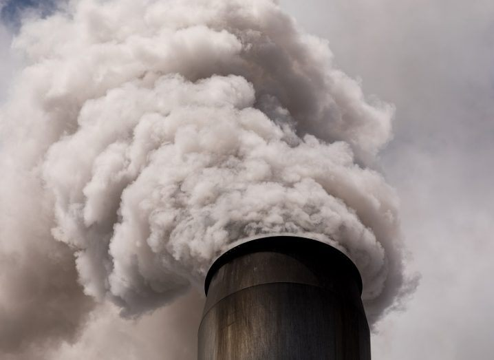 Single smoke stack billowing out carbon emissions against a grey sky.