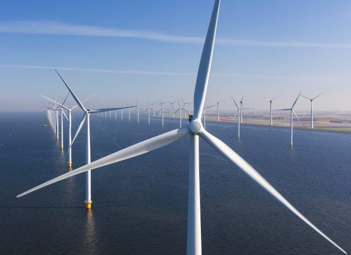 Large offshore windfarm, with rows of turbines in the sea.