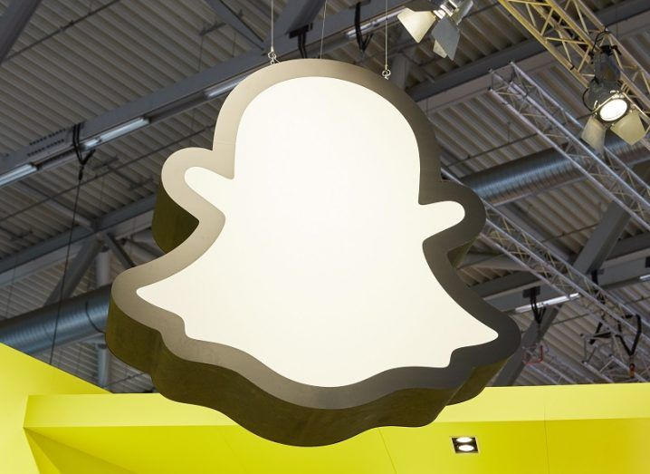 The Snapchat ghost logo hanging from a conference hall ceiling.