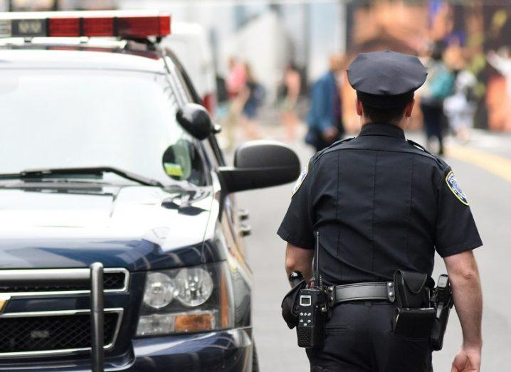 Shot of behind a police officer beside a car on a busy street.