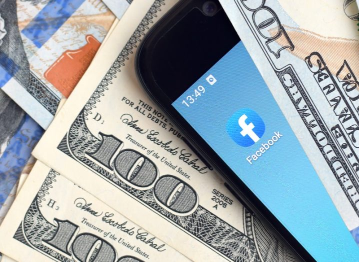 A phone with the Facebook app sandwiched between 100 dollar bills.
