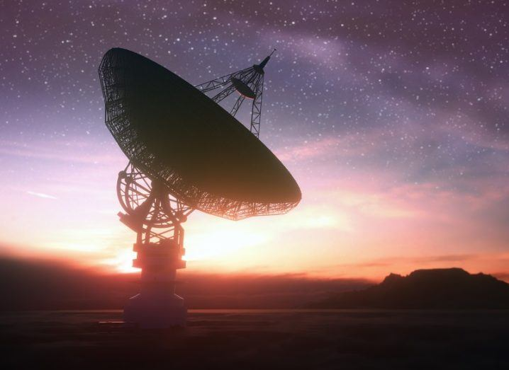 Huge satellite antenna dish searching for radio signals in space at sunset.