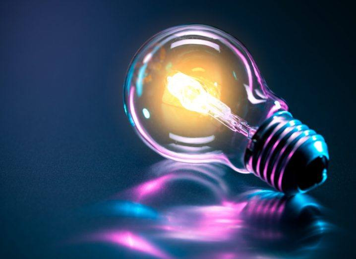 A light bulb shining against a blue and purple background.