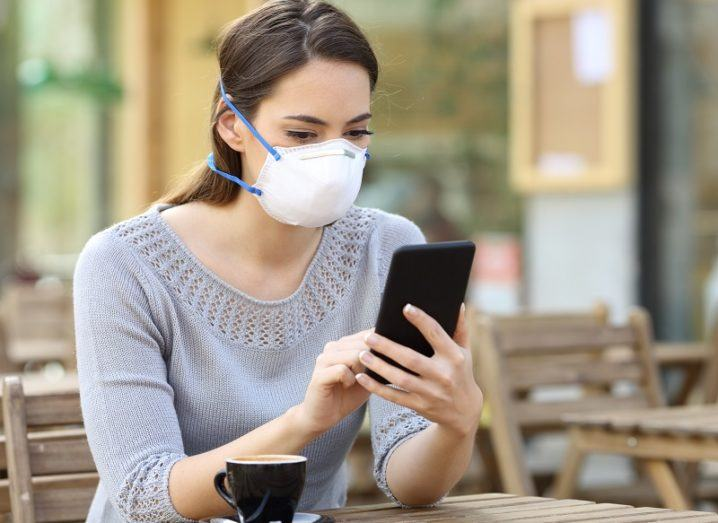 Woman wearing a facemask while sitting at a table with a coffee while looking at a phone.