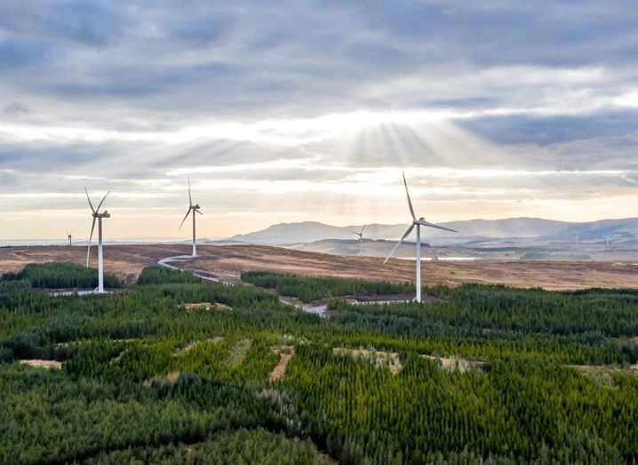 Aerial view of the Clogheravaddy wind farm in County Donegal with sun peering through clouds.