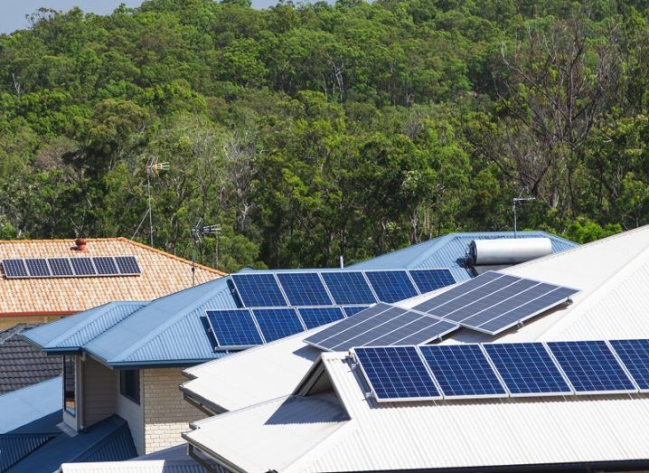 Solar panels on the roofs of three houses.