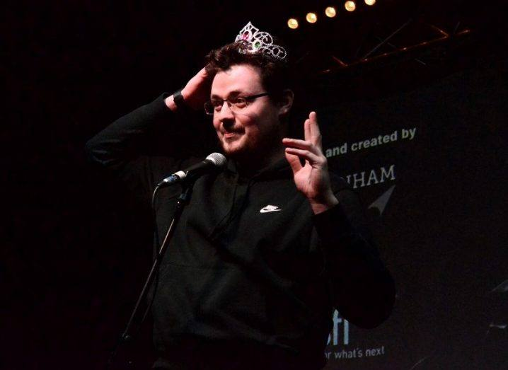 Conor Duffy wearing a child's plastic tiara on stage in front of a microphone.