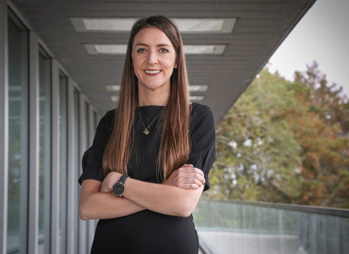 Dr Eimear Dolan smiling and standing with her arms folded in front of a building and trees.