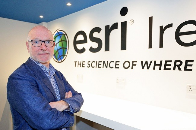 Eamonn Doyle in a blue blazer crossing his arms in front of the Esri Ireland logo.