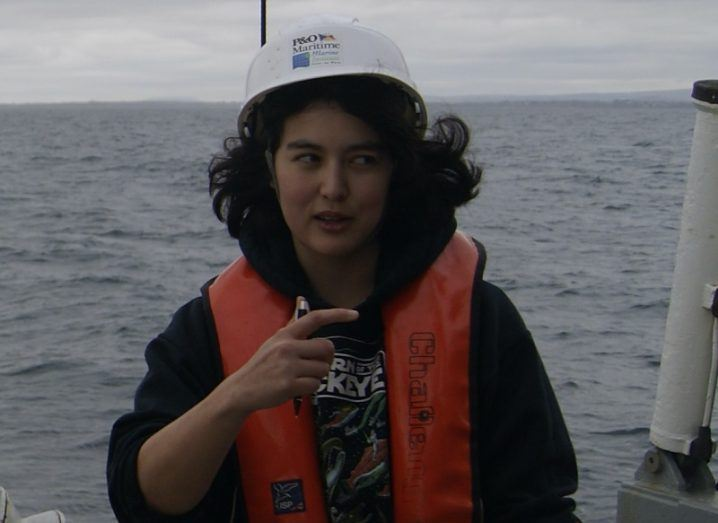 Elena Pagter wearing a lifejacket and a white hardhat on board a research vessel on the ocean.
