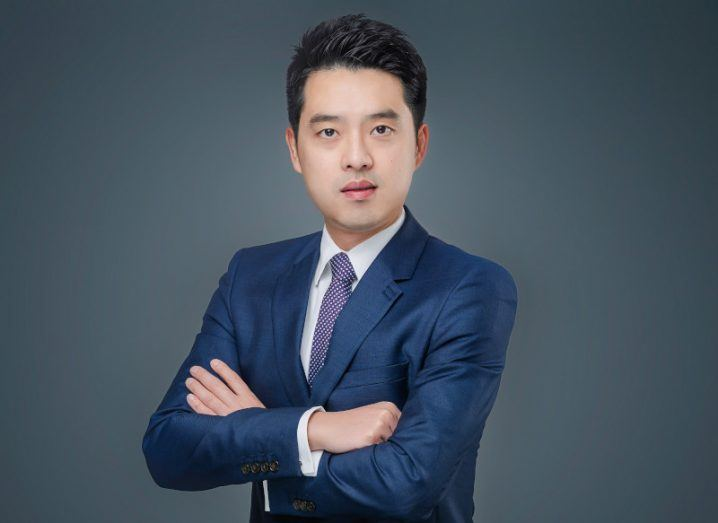 Jijay Shen, CEO of Huawei, wearing a blue suit with arms crossed, standing against a grey background.