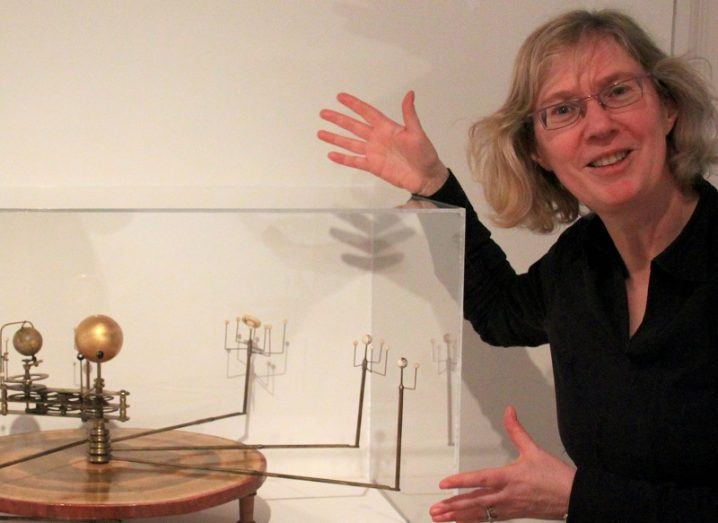 Mary Mulvihill in a black shirt and smiling while showing a model of planetary orbits.