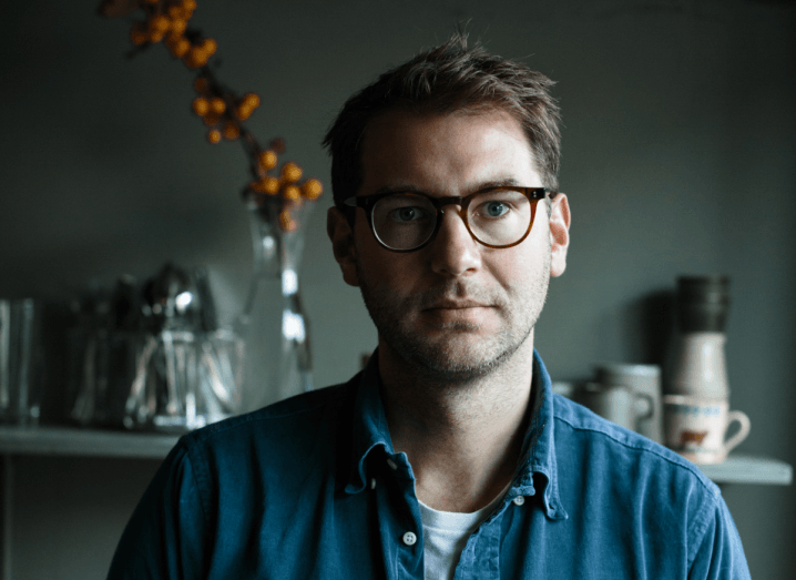 Image of a man wearing glasses and a blue denim shirt sitting in a dark kitchen.