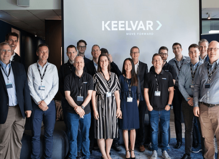 The Keelvar team standing in front of a projector with the company logo.