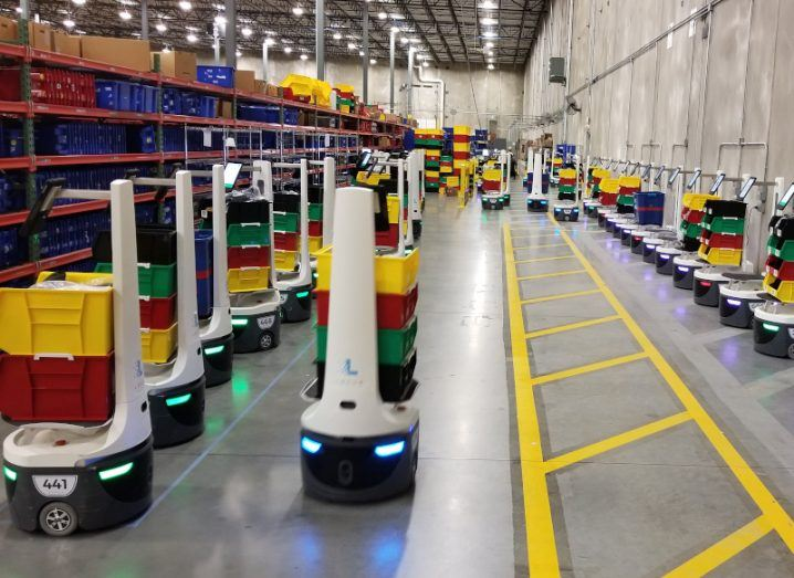 Image of robotic devices lined up in a warehouse.