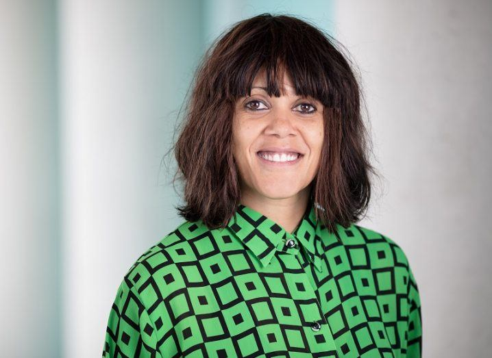 Headshot of Prof Annette Byrne, director of the NPIC, smiling in a green and black top against a blurred white background.