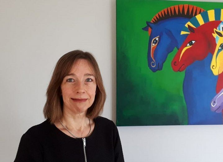 Sandra Hurley standing and smiling beside a multicoloured art piece featuring horses.