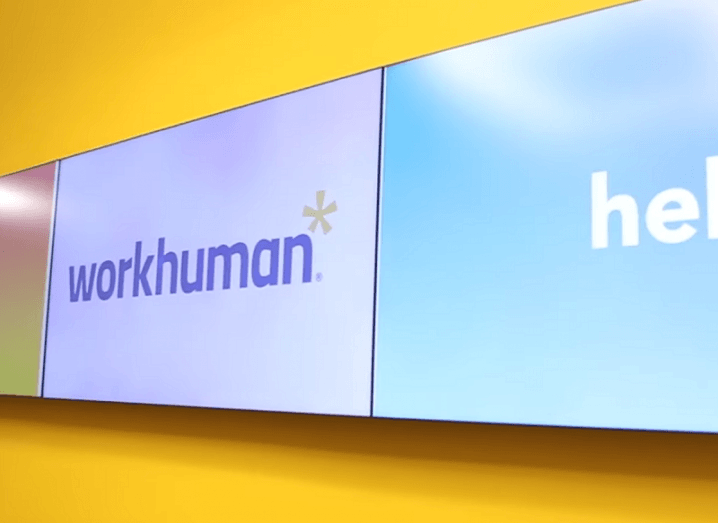 The Workhuman logo on a TV screen against a yellow wall.