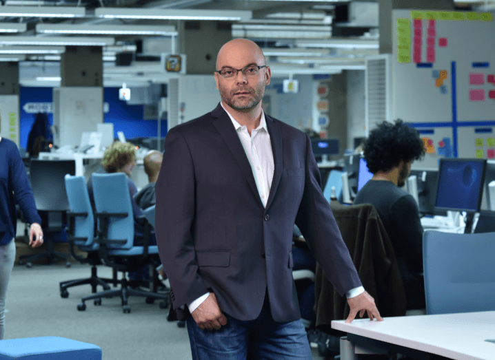 A man in a black blazer, blue jeans and a pink shirt stands in an office.