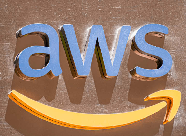 The AWS logo on a brown wall.