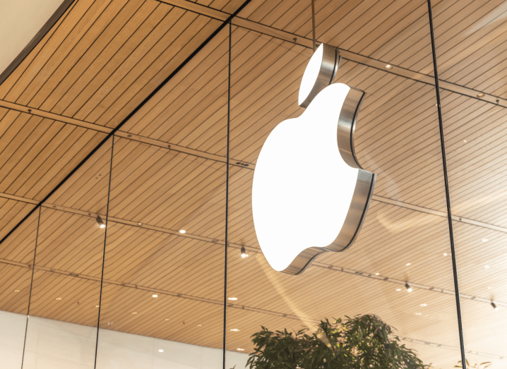 The Apple logo displayed on a glass window under a wooden panelled roof.