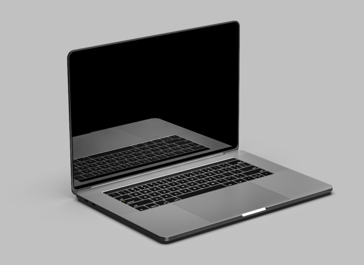 An Apple laptop opened up in front of a grey background.