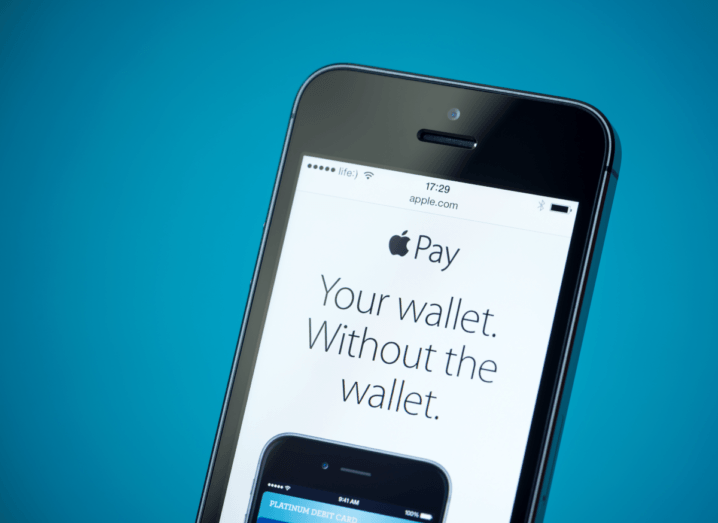 An iPhone 5S showing the Apple Pay website on screen.