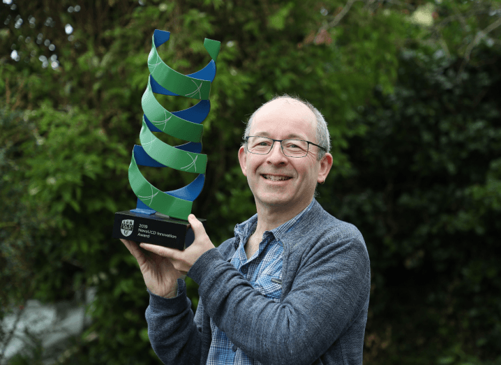 A man standing outdoors holding a large green and blue award statue.