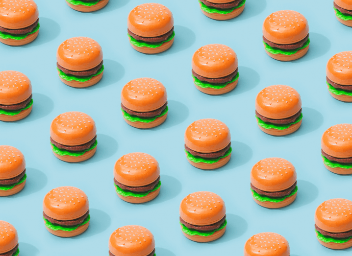 Dozens of small burgers on a blue background.