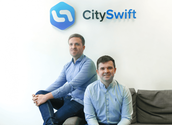 Two young men wearing blue shirts sitting on a sofa underneath a CitySwift sign.