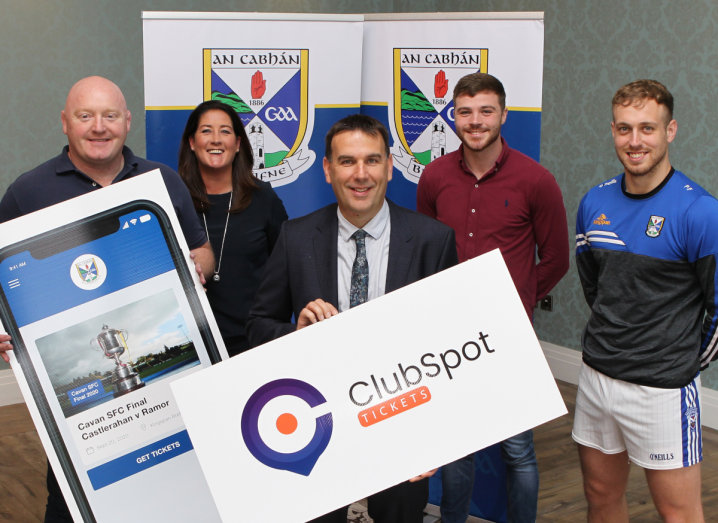 A group of people standing beside each other holding large ClubSpot signs.