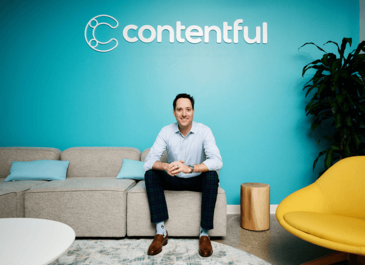 A man sitting on a grey couch in a blue room, with the Contentful logo on the wall behind him. He is wearing a blue shirt, black trousers, blue socks and brown shoes.